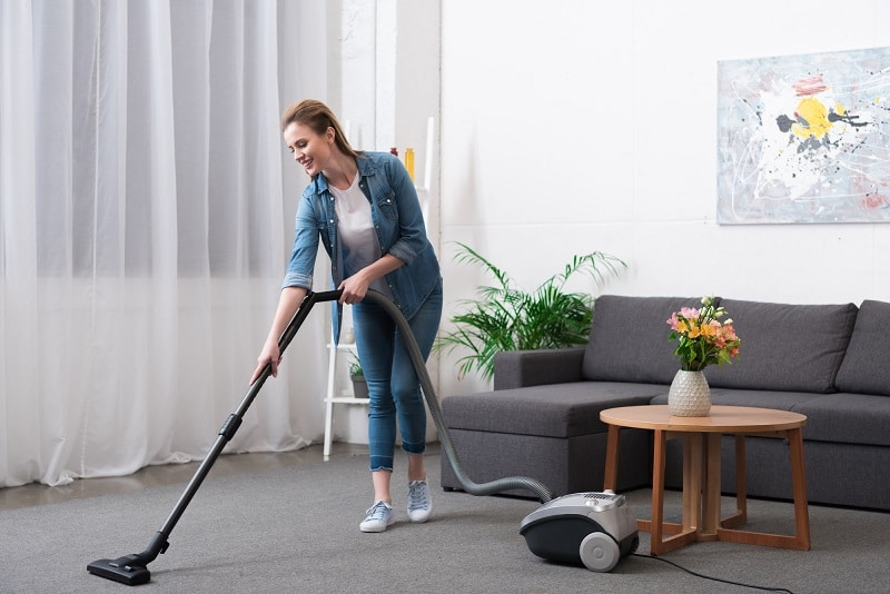 woman vacuuming with canister vacuum