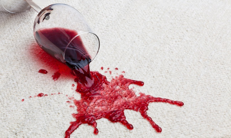 a fallen glass of red wine with a dirty carpet.
