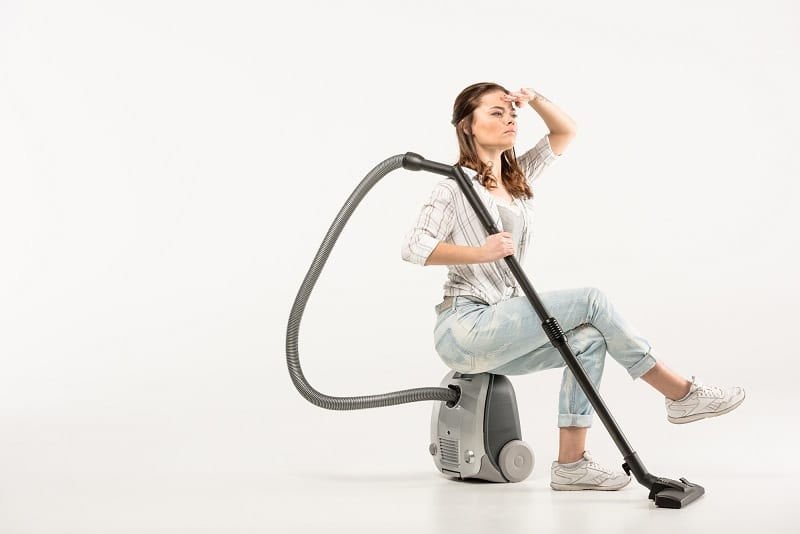 woman sitting on vacuum cleaner - searching for the best vacuum