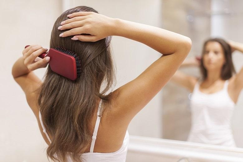 brushing shiny hair with clean hair brush