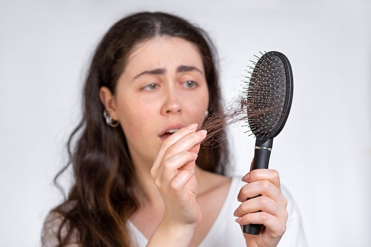 woman frustrated pulling hair from a dirty hair brush