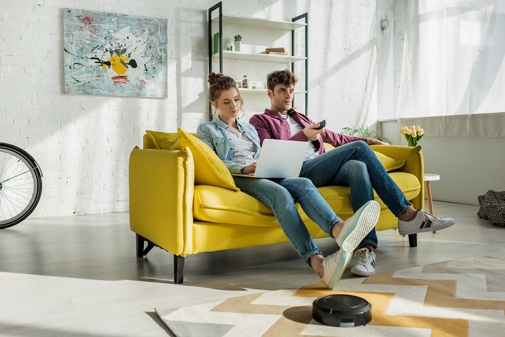 best robot vacuums save you time - couple relaxing on couch while robot vacuum cleans floor