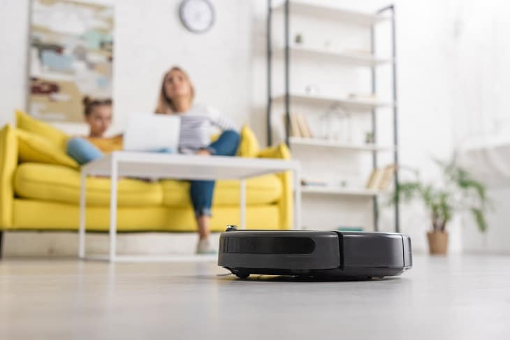 how to choose the best robot vacuum - mother and daughter relaxing while robot vacuum cleans floor